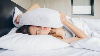 How to sleep with anxiety: a woman holds a pillow while lying in bed worrying