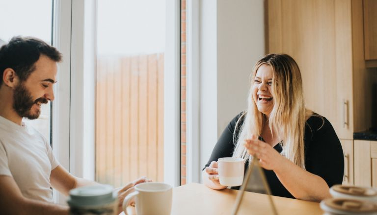 couple laughing and drinking coffee