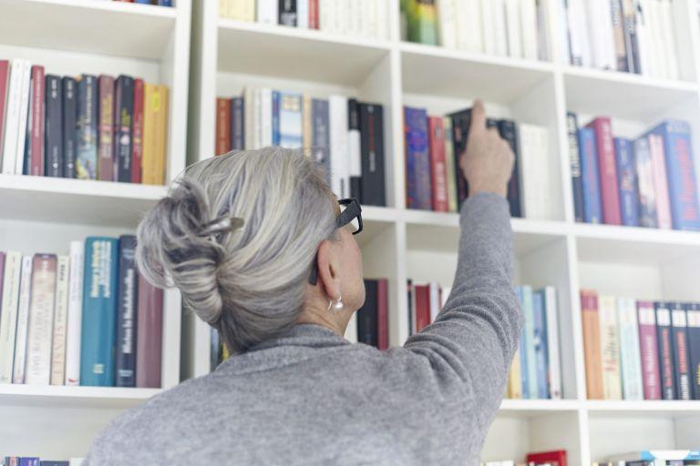woman taking book off bookshelf