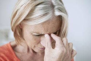 An older woman holds her head in pain.