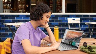 Man sitter med laptop vid bord ute.