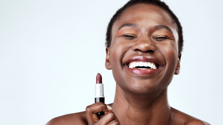 Woman smiling holding a lipstick depicting easy makeup looks