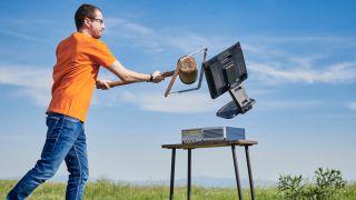 Mand slår en desktop pc med en mukkert