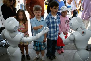 Children interact with Aldebaran's Pepper robot during the Defense Advanced Research Projects Agency (DARPA) Robotics Challenge Expo at the Fairplex June 6, 2015 in Pomona, California.