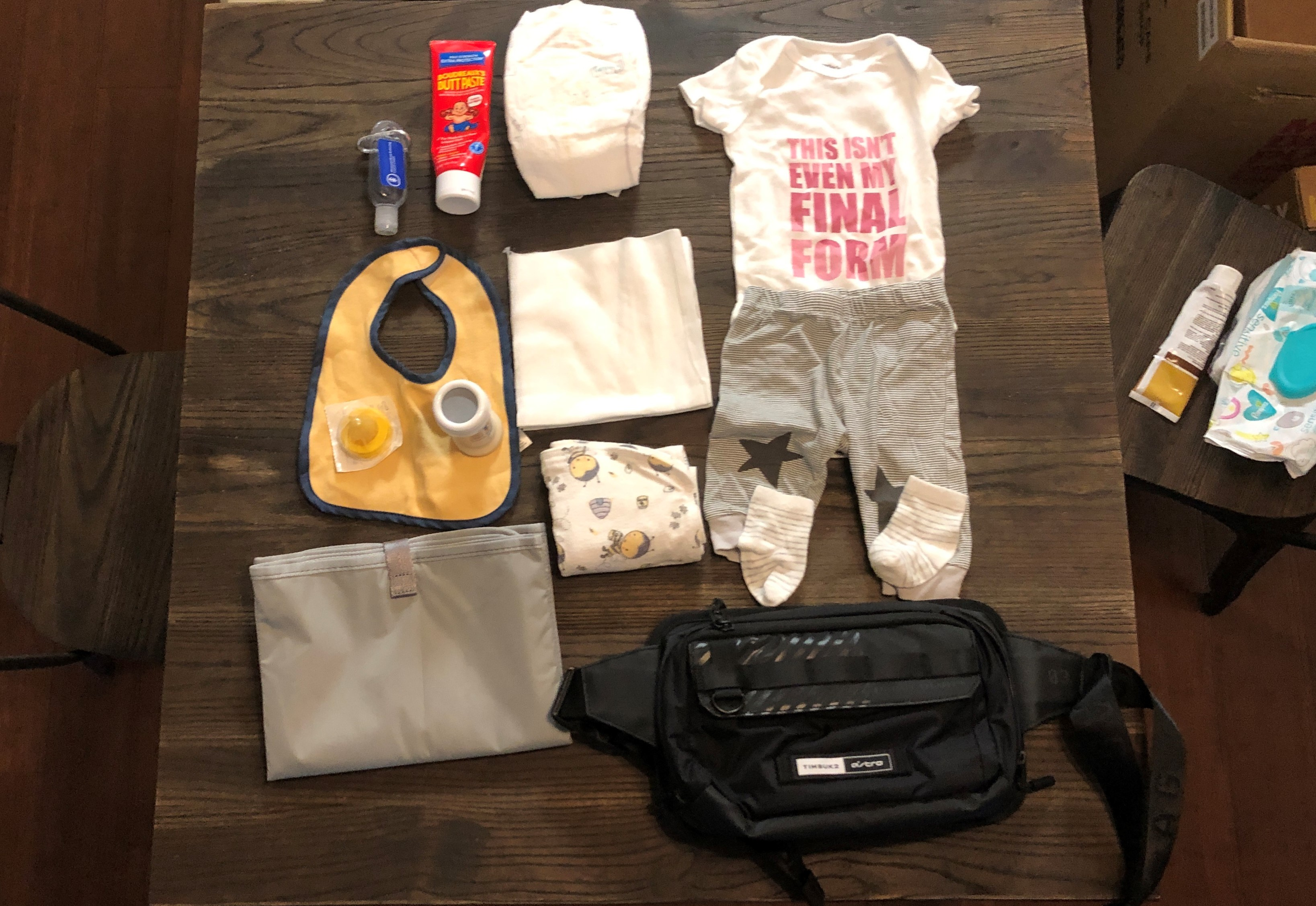 Cross body bag on table with various baby items.