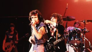 Bon Scott and guitarist Angus Young of AC/DC put on a show for the crowd circa 1977 in Hollywood, California.
