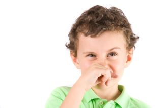 A little boy coughs and wipes his nose.