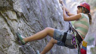 A woman rapelling down a cliff