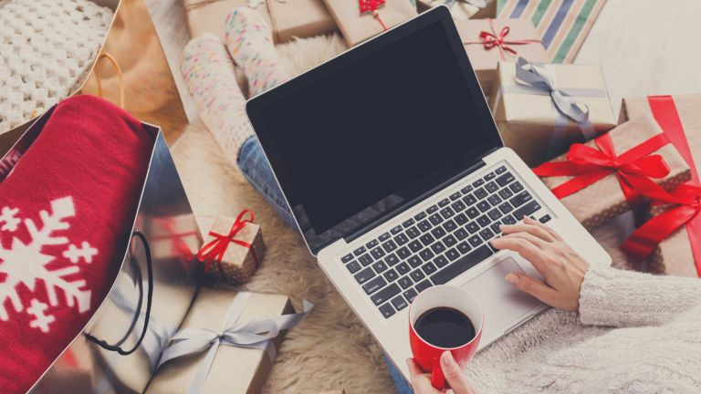 Christmas gift cards: Christmas shopping on laptop with presents around