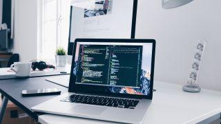 laptop displaying code on a desk alongside a phone and desktop