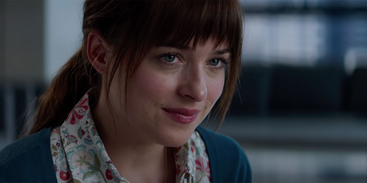 Dakota Johnson with her hair pulled back and kind of messy while conducting an interview in the Fifty Shades Of Grey trailer.
