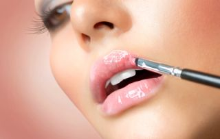 A woman applies lipstick.