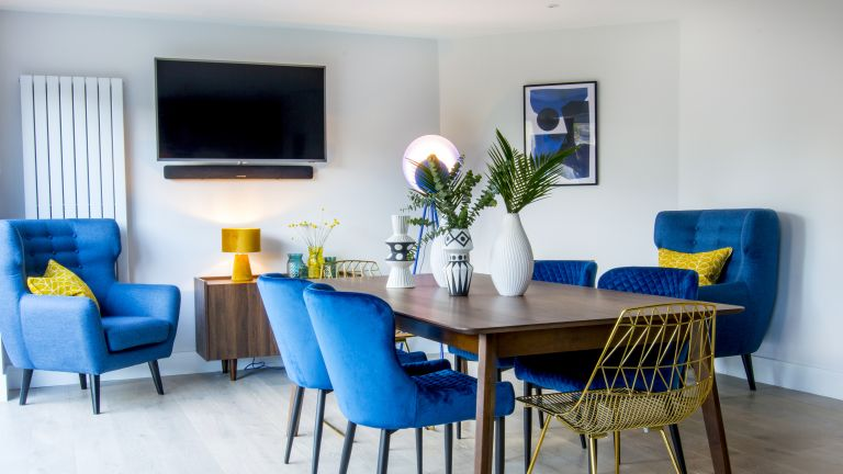 How to mount your TV to a wall Blue velvet dining room chairs in a dining room with wall mounted TV