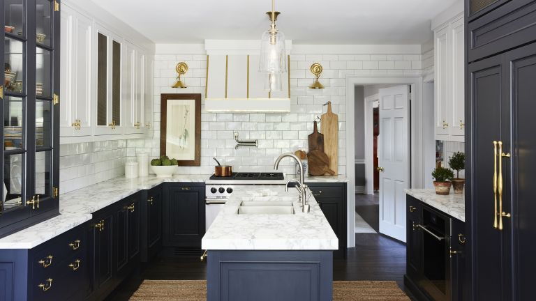 A kitchen with navy cabinetry, white tiled walls and brass hardware