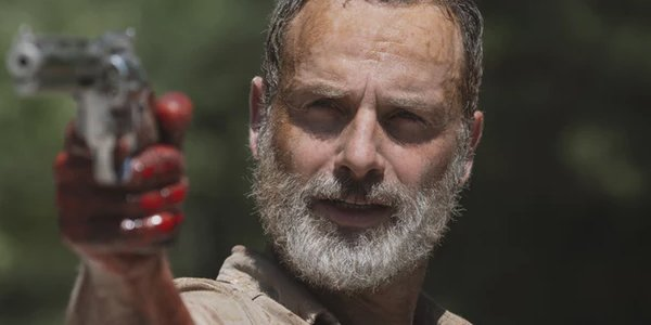 Andrew Licoln as Rick Grimes holding a gun in his last Walking Dead episode