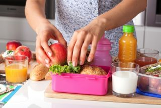 A woman makes a lunch in a lunch box.