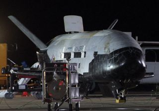 Despite its robotic nature, the X-37B space plane received a warm welcome from Air Force crews at Vandenberg. Here, the vehicle appears to be undergoing safing procedures after landing on Dec. 3 at 1:16 a.m. PST (0916 GMT). Significant weathering, or disc