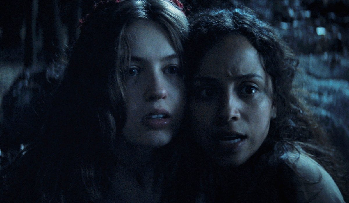 Olivia Welch and Kiana Madeira huddled together in the woods in Fear Street: Part 3 - 1666.