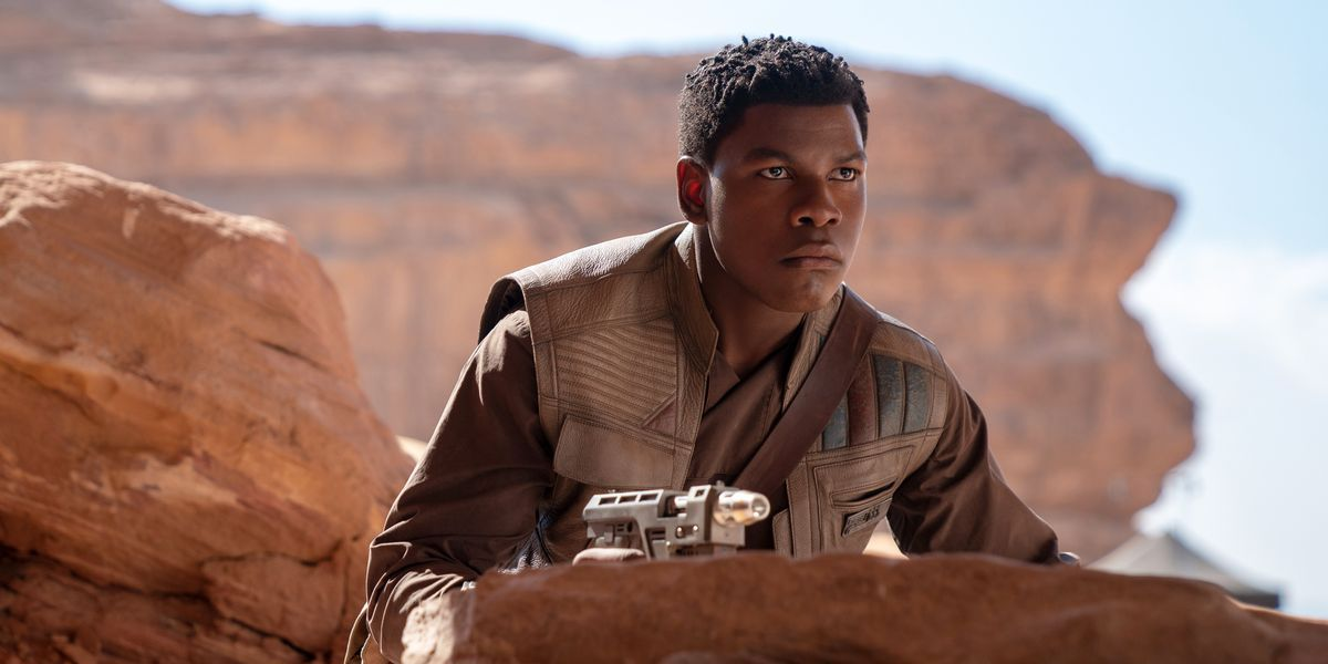 Finn (John Boyega) crouches behind a rock in 'Star Wars: The Rise of Skywalker'