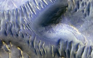The mound in the center of this image — which was captured by the HiRISE camera aboard NASA's Mars Reconnaissance Orbiter in April 2009 — appears to have blocked the path of sand dunes as they marched across the scene.
