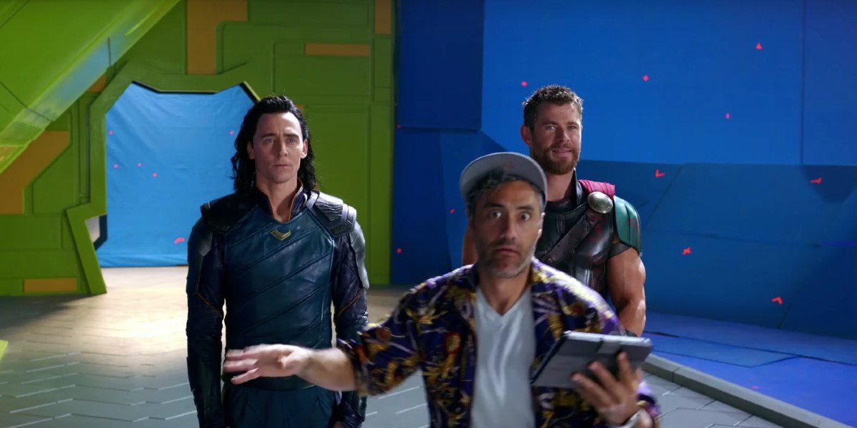 Thor: Ragnarok Taika Waititi goofing off in front of Tom Hiddleston and Chris Hemsworth