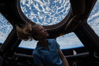 NASA astronaut Karen Nyberg enjoys the view of Earth from the windows in the Cupola of the International Space Station during her Expedition 37 mission in 2013. Image taken Nov. 4.