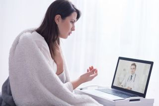 A woman consulting with a doctor via online video chat.