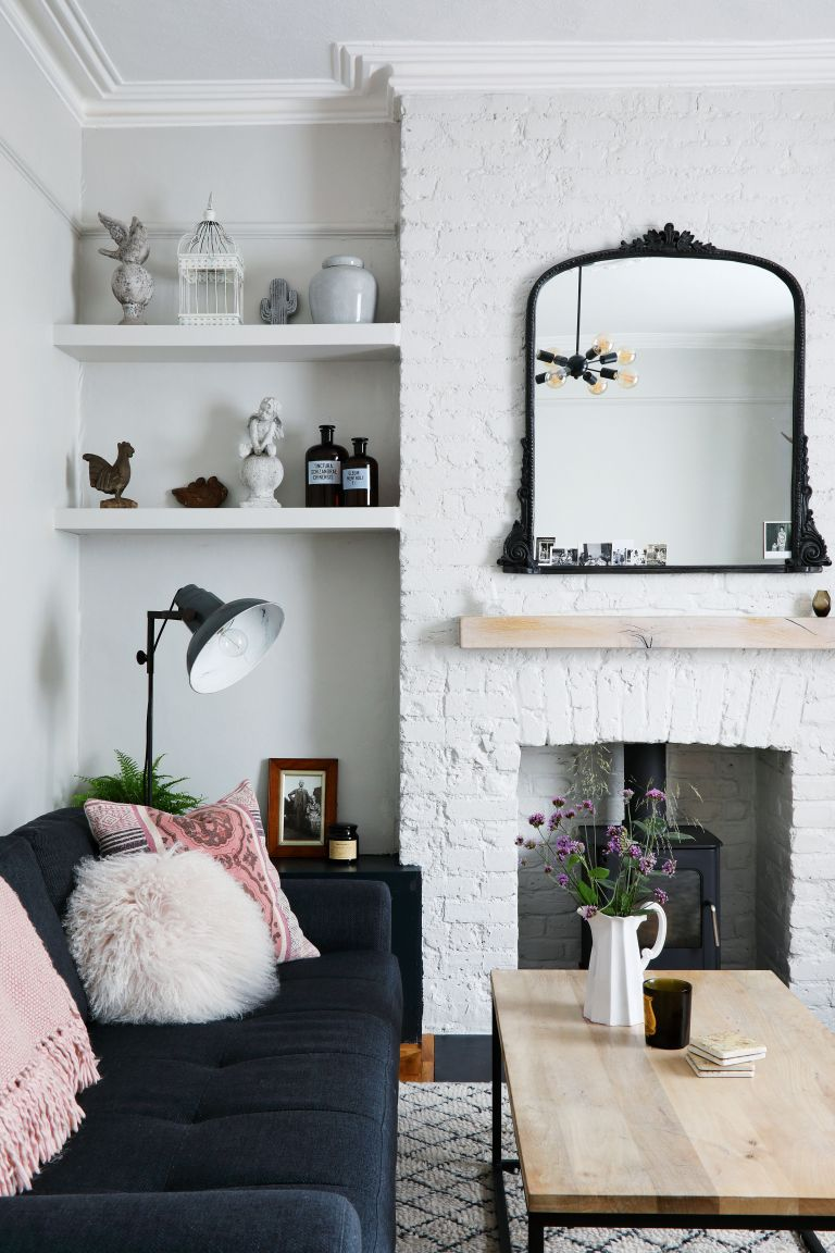 white living room with dark grey sofa and large mirror