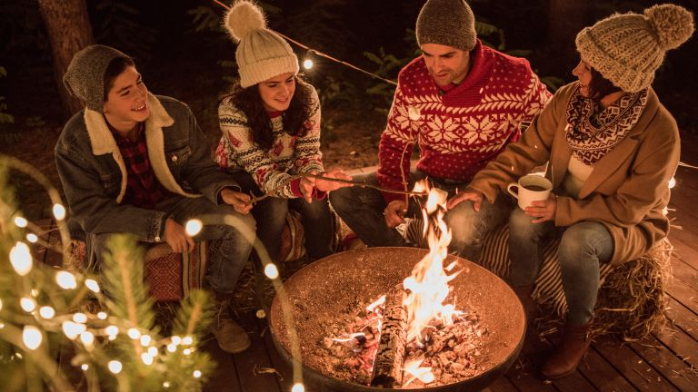 family toasting marshmallows over a fire pit