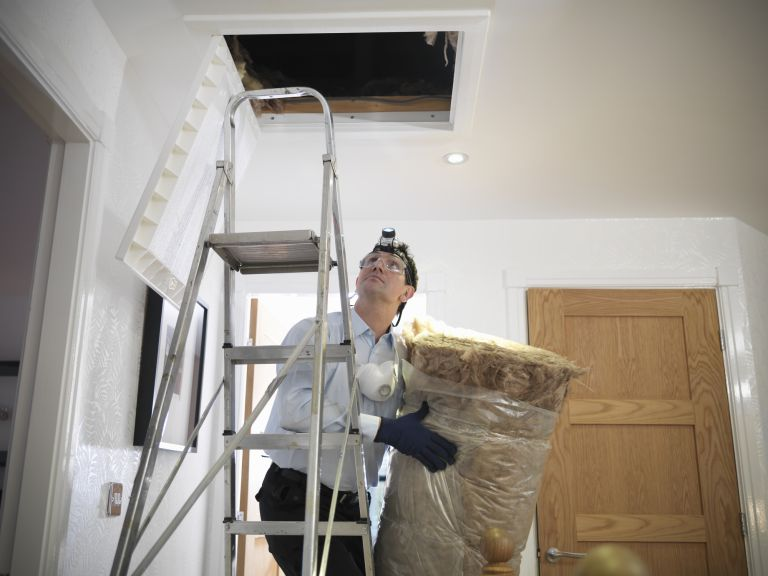 man insulating an attic