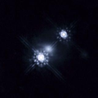 This Hubble picture shows a quasar that has been gravitationally lensed by a galaxy in the foreground, which can be seen as a faint shape around the two bright images of the quasar.