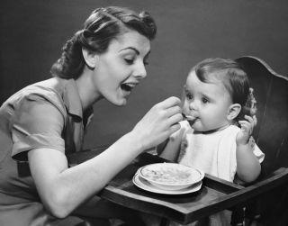 1950s mom feeding her baby.