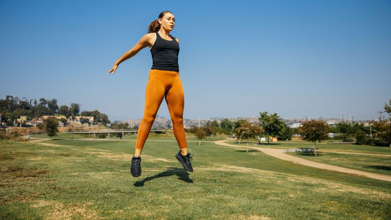 Plyometrics workout challenge: woman doing jumping exercises in a park