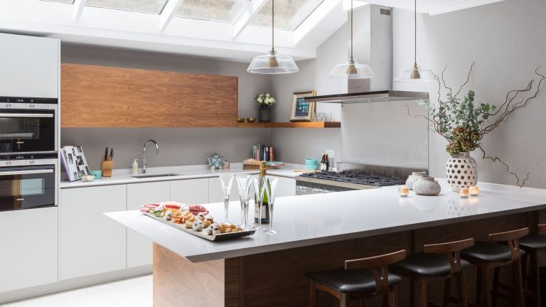 An example of U-shaped kitchen ideas illustrated by a sleek pale gray scheme with skylights and pendant lighting.