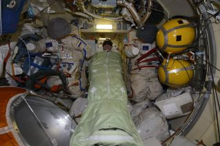 NASA astronaut Chris Cassidy snoozes in a sleeping bag in a Russian airlock on the International Space Station instead of its U.S. segment in this photo by crewmate Ivan Vagner of Roscosmos as engineers on the ground work to isolate a small air leak in another module.