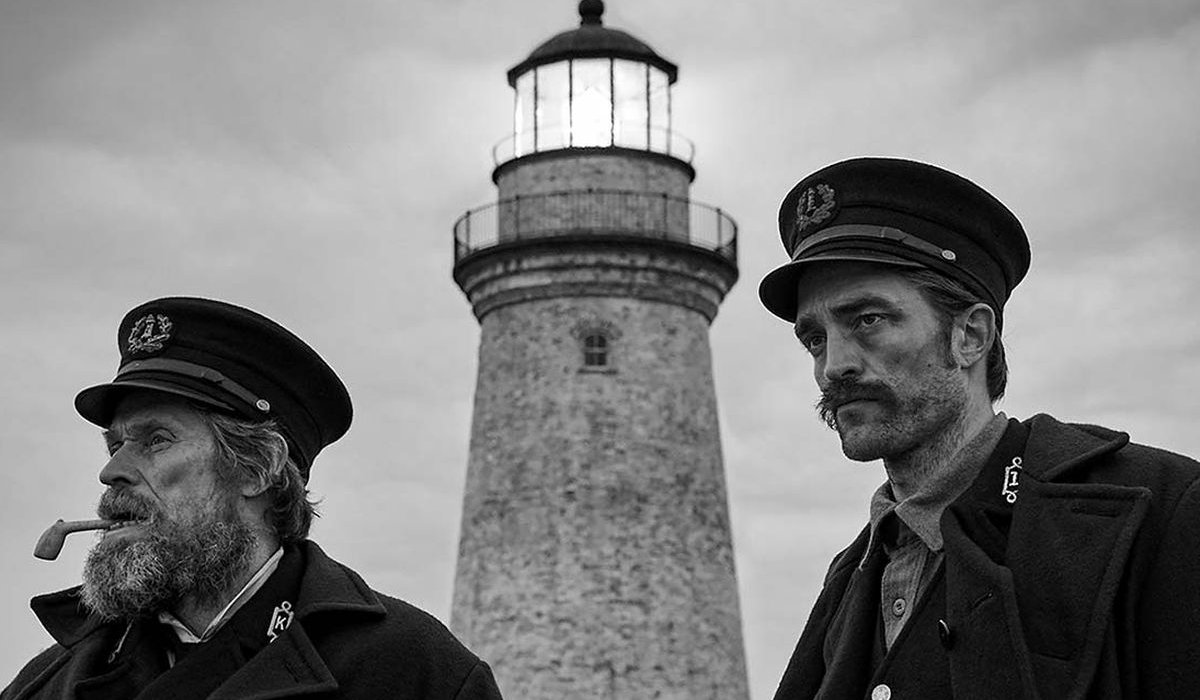 The Lighthouse behind Willem Dafoe and Robert Pattinson outside