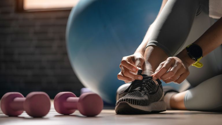 best dumbbells: woman tying shoe lace with dumbbells next to her feet