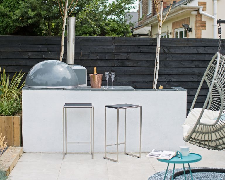 Sleek white garden bar ideas with an outdoor oven, metal bar stools and a black painted fence behind.