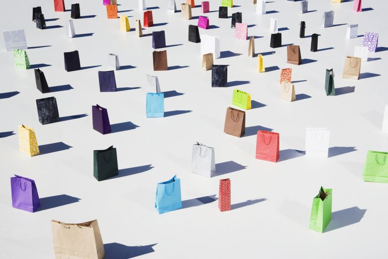 Lots of paper shopping bags in a variety of colors stood upright on a white floor
