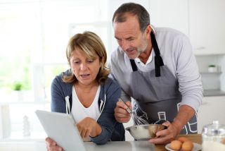 A couple cooks together while checking a recipe on their tablet.