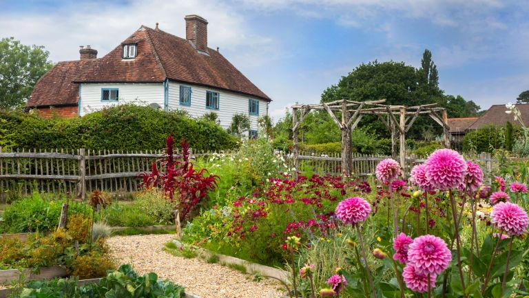 Exterior of white clapboard Grade II listed farmhouse in Sussex