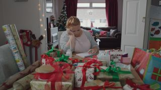 Casualty Robyn at home surrounded by Christmas presents