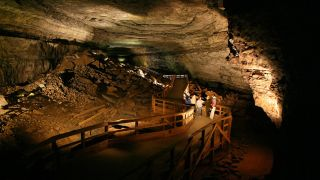 A park ranger talks with Mammoth Cave visitors in Broadway, one of the cave's canyon passages.