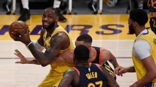 LeBron James #23 of the Los Angeles Lakers controls the ball as Draymond Green #23 and Stephen Curry #30 of the Golden State Warriors defend during the first half of an NBA Tournament Play-In game at Staples Center on May 19, 2021 in Los Angeles, California.