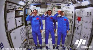 The crew of China's Shenzhou 12 mission salute for a photo inside the Tianhe core module of the Tiangong space station after successfully docking at the module on June 17, 2021.