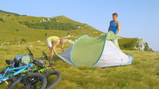 best pop-up tents: campers setting up a pop-up tent