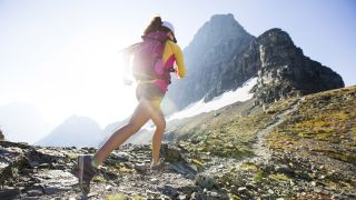 A woman trail running in the mountains