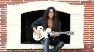 A shot of Yngwie Malsteen sat in a window holding a guitar
