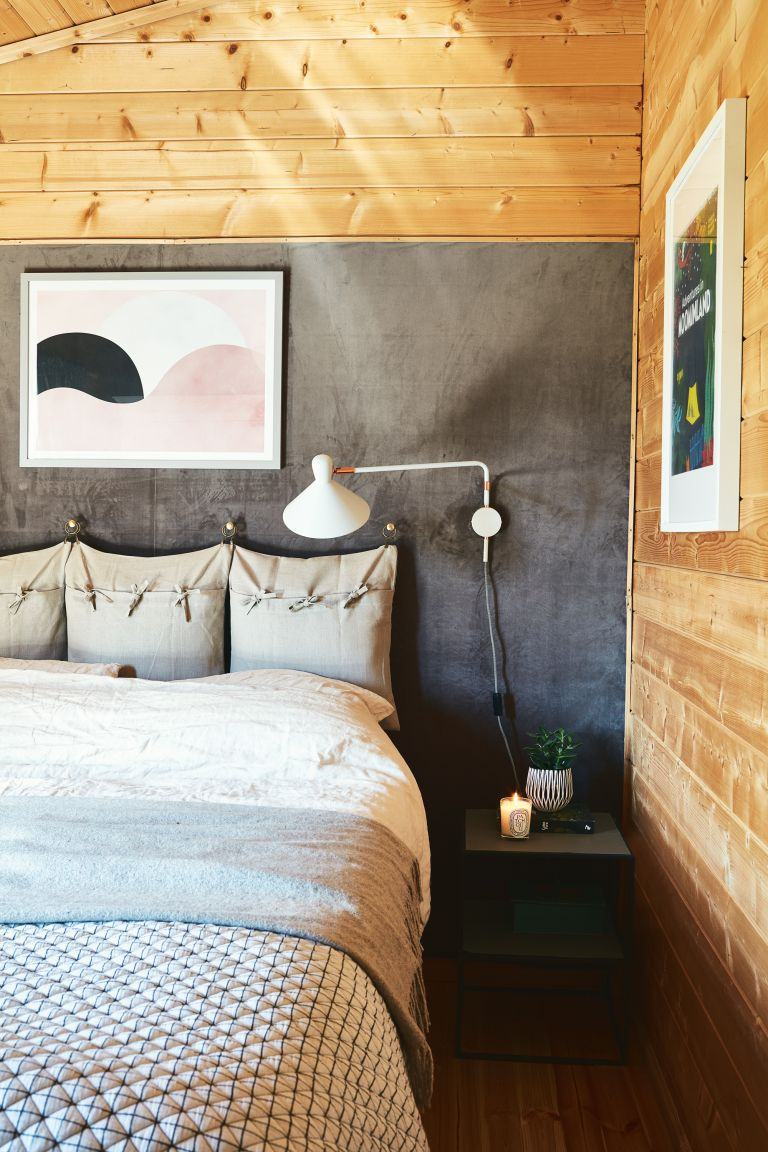 Smart plugs: A close-up of a bed against a grey velvet wall covering in place of a headboard