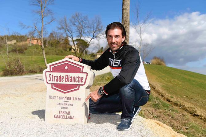 Fabian Cancellara next to the Strade Bianche milestone dedicated in his honor